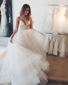 Vestido de noiva verão, com decote frontal e alcinhas. Na altura do estômago, o tecido é todo trabalhado em pedras e a saia é totalmente fluida, cheia de camadas.