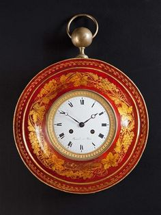 A Charles X Red Tole Cartel Clock (France) 1820. - An early nineteenth century tole circular wall clock, with painted decoration of gold vine leaves and grapes on a red ground, the white enamel face within an ormolu border, signed Bovard à Paris (active 1806-1830), surmounted by a brass finial and brass ring support.