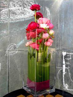 Arreglo floral de ranúnculos en florero alto de vidrio.