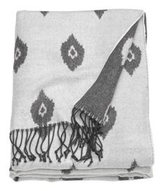 White/gray patterned. Throw in soft, jacquard-weave fabric with fringe on short sides.