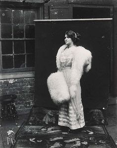 """Photograph of Storyville prostitute, by E. J. Bellocq, circa 1912. """"Storyville Girl Posing Out of Doors"""" with backdrop."""