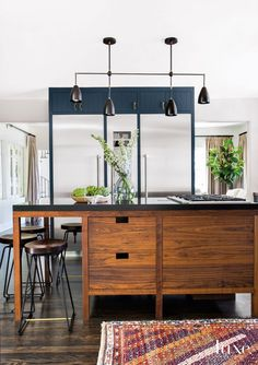 Custom aged-brass-steel-and-walnut adjustable barstools pull up to a walnut island featuring a honed black granite countertop in the kitchen. A blackened-metal-and-brass light fixture by Apparatus illuminates the scene.
