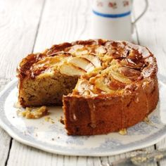An apple cake with a slice cut out drizzled in sauce