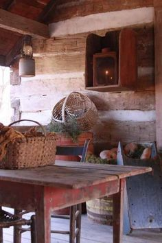 Love these log walls., table, baskets, & hanging cupboard. Wonderful. very primitive