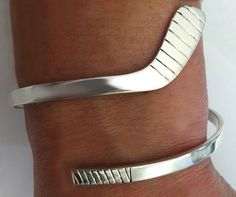 "This is a flat solid ice hockey stick wrap around bracelet in sterling silver. The blade itself is about 7/8"" long and approx 1/3"" wide. Shaft is about 5mm wide. Bracelet itself starts out measuring a"