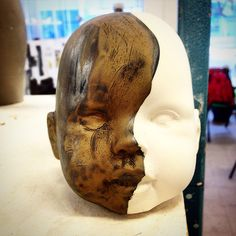 Ceramic doll head with a bronze and gold metallic glaze  over the top :)