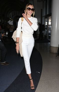 """Candice Swanepoel worked all-white the practical way with a fitted top and high-waisted trousers — then added a pair of ankle-strap heels for a look that says """"frequent flier-meets-Summer-styler."""""""