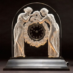 R. LALIQUE CLEAR AND FROSTED GLASS DEUX  FIGURINES CLOCK  Circa 1926  Wheel carved: R. LALIQUE, FRANCE  14-5/8 inches high (37.1 cm)
