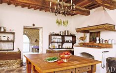 18th-century farmhouse in Tuscany, features a hood framed with antique beams and a bold stone floor.