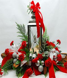 A Norfolk Florist Exclusive this Traditional Silver Lantern is Designed as a Centerpiece for Your Large Family Gathering. It features Fragrant Evergreens, Red Carnations, Silver Christmas Decorations Accented with Red and Silver Velvet Ribbons. A Great Gift for the Office Party or Your Family Gather. Measures 36 inches wide by 16 inches wide by 24 inches tall. THIS IS A SPECTACULAR CENTERPIECE!!!
