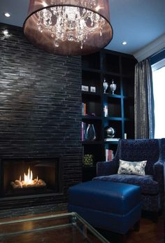 by Lucid Interior Design Inc  Black & Navy Elegance......fireplace wall of stone and black floor to ceiling bookshelves