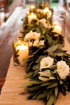 simple garland runner with candles and loose flowers instead of centerpieces
