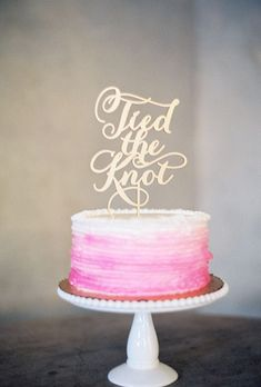 A one-tiered pink-and-white wedding cake with a gold laser-cut cake topper | Brides.com
