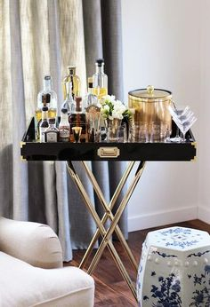 Living room features sofa next to a glossy black lacquer tray table bar fitted with brass campaign ...