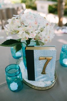 vintage books + house numbers, photo by Joe+Kathrina http://ruffledblog.com/whimsical-san-juan-capistrano-wedding #weddingideas #tablenumbers
