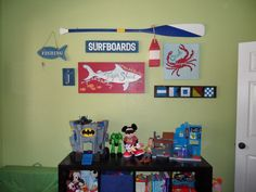 I removed the changing table & wall cabinet from Jason's room, and moved the dresser to another wall.  It left me with a lot of open floor and wall space, so this is what I did to his wall.  PBK oar, shark & crab plaques, and buoy.  'Gone fishing' and 'j' were already in his room, just moved them into this grouping.  I made the 'surfboards' and nautical flags signs.  'Surfboards' was inspired by a PBK sign, but my version was 1/4 the price.