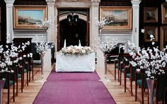 wedding ceremony flowers in the Picture Gallery at Royal Holloway, Wedding aisle with floor standing vases of cherry blossom, and a ceremony table long display of ivory and coral wedding flowers. Royal Holloway wedding flowers. More at www.TheFineFlowersCompany.co.uk