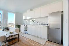 kitchenette blanche avec plancher eb bois et crédence en verre blanche