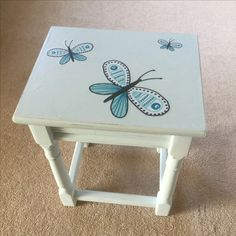 Dark wood side table painted, with added butterfly stickers and varnished