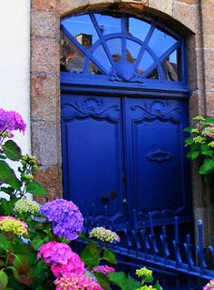 Cobalt blue door and matching iron railing with pink and purple flowers