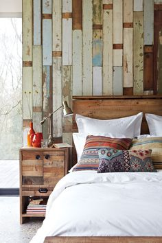 Beautiful bedroom. Reclaimed timber wall paired with raw woodwork, white linen & Kilim cushions.