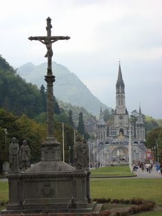 Our Lady of Lourdes Basilica in Lourdes, France ; with Pyrenees mountains in the background.