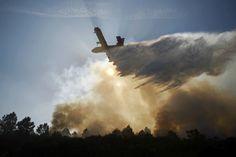 Un avión rocía agua sobre la villa de Vouzela, Portugal en la lucha de cientos de bomberos por extinguir los crecientes incendios forestales. (AP)