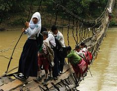A very different world: Children make their way across a collapsed bridge to get to school in Indonesia.