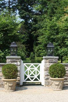 Stone wall : Gate : Lanterns : Boxwood planters