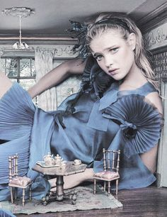 "Natalia Vodianova stars as Alice in the fairytale editorial 'Alice In Wonderland' shot by Annie Leibovitz and styled by Grace Coddington for Vogue US December 2003      ""How was Alice to know the innocent little bottle would make her grow to such a size? As Helmut Lang watched from the wall, she curled her legs up and hoped the designer's organza minidress wouldn't be crushed by her newly found starling height."""