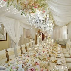 This draping and floral ceiling installation is incredible, luxe, and elegant. The chandeliers and white add the perfect feel for a beautiful wedding design.