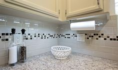 This backsplash: Daltile Urban Putty 3 X 6 gloss subway tiles in a brick set pattern with an accent strip of MSI Ibiza glass and stone blend 1 X 1 mosaic tiles.