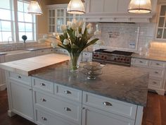 Not sure how I feel about the butcher block area on the island, but I love the white cabinetry and the gray marble slabs - Brazilian Arabescato Quartzite
