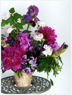 Peonies, sweet peas, and iris in a birch container.