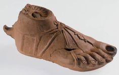 A Roman lamp, made in the shape of a foot. It would have been filled with oil.