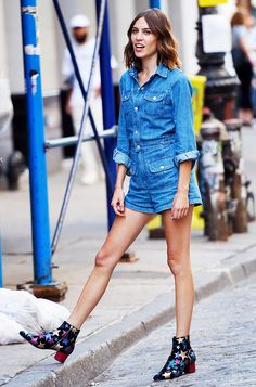 Alexa Chung wears a denim jumpsuit with patterned boots