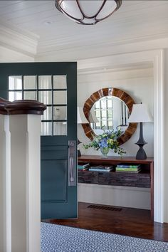 Great coastal foyer design. In this foyer, I really like the contrast of the front door paint color against the neutral walls and also the hardwood floors in herringbone pattern.