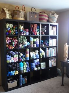 Craft room - Expedit yarn storage.  Like the pattern tote and knit baskets on top #craftroom #yarn #ikea