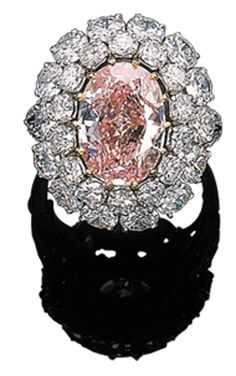 A HIGHLY IMPORTANT DIAMOND AND FANCY INTENSE PINK DIAMOND CLUSTER RING  Set with an oval-cut fancy intense pink diamond weighing 7.34 carats in a circular-cut diamond surround to the circular-cut pierced shoulders and platinum hoop, with French assay marks  Mount by Van Cleef & Arpels, no. 20377