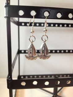 Tiny silver sailboat dangle earrings. $5