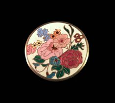1940s French floral champleve cloisonne enamel brooch pin. The brooch represents a multicolor enameled flowers bouquet with vivid pink, red, yellow , purple and blue enamels contrasting with a white background. The circular brooch is made of brass metal and it has a trombone style clasp. The