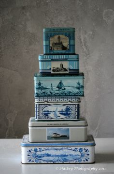 A stack of tins. Tins are great utilized to hold tea, buttons, paperclips, etc. These blue and white tins feature quaint Dutch scenes.