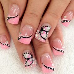 A beautiful and creative French tip design perfect for your nails. Clear polish is used as based with baby pink polish for the French tip. Slim butterfly details and curves are then added plus silver beads for effect.