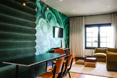 Green, patterned walls in light wood space
