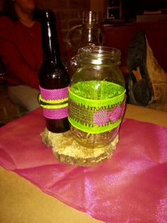 Center pieces for pink, green & brown rustic wedding.  Beer bottles, mason jars, liquor/whiskey bottles on wooden rounds.