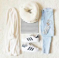 White oversized cardigan featuring a large white infinity scarf, and a black and white striped shirt. Paired with light wash jeans and Adidas Superstar sneakers.