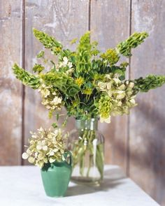 Green is the quintessential color of spring -- give it more prominent display in your bouquet! The small vase holds green hydrangeas; behind it is an arrangement of euphorbias, hydrangeas, and bells of Ireland.