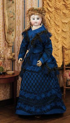 "Theriault's Antique Doll Auctions - French Bisque Poupee Attributed to Adelaide Huret with Articulated Wooden Body - 18"" (46 cm.) Attributed to Adelaide Huret,circa 1870 - Lovely and rare wooden-bodied poupee,wearing fine antique royal blue patterned silk costume with black silk fringe."