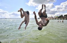 (Aug 02 2020) Men jump from a jetty into the water as the hot weather continues, at Southend-on-Sea, in England. (Victoria Jones/PA via AP)