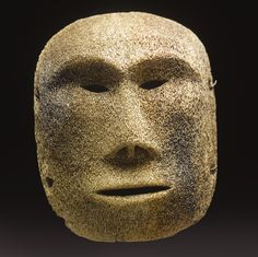 ESKIMO WHALEBONE MASK    of convex form, carved with a naturalistic face, the mouth, nostrils and eyes pierced; pairs of drilled holes at each side for suspensions.  height 8 in.